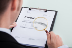stock-photo-47373190-businessman-examining-invoice-through-magnifying-glass